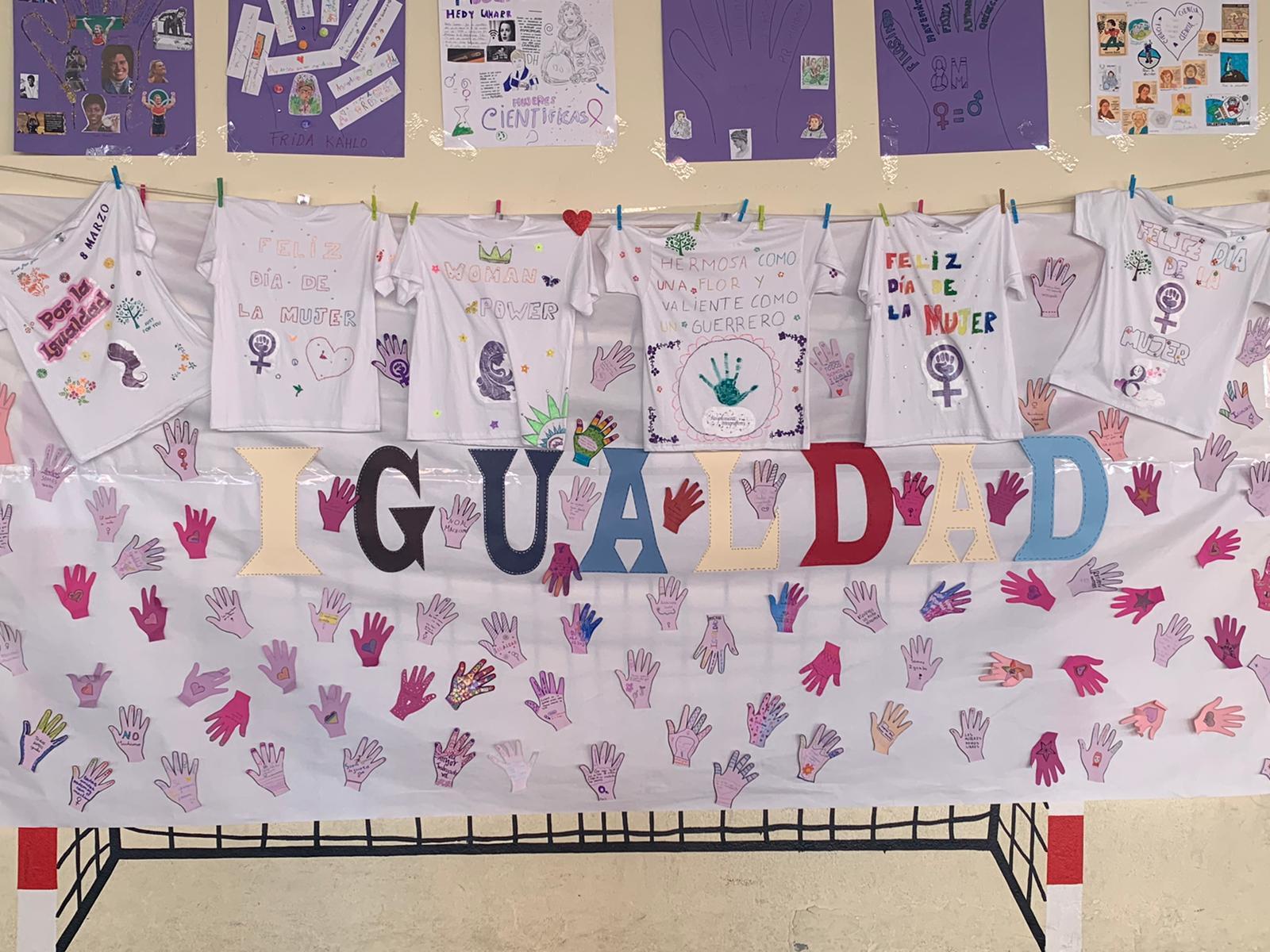 Pancarta que pone IGUALDAD con manos moradas y mensajes por el 8M. Carteles con mujeres relevantes, científicas, pintoras, etc..