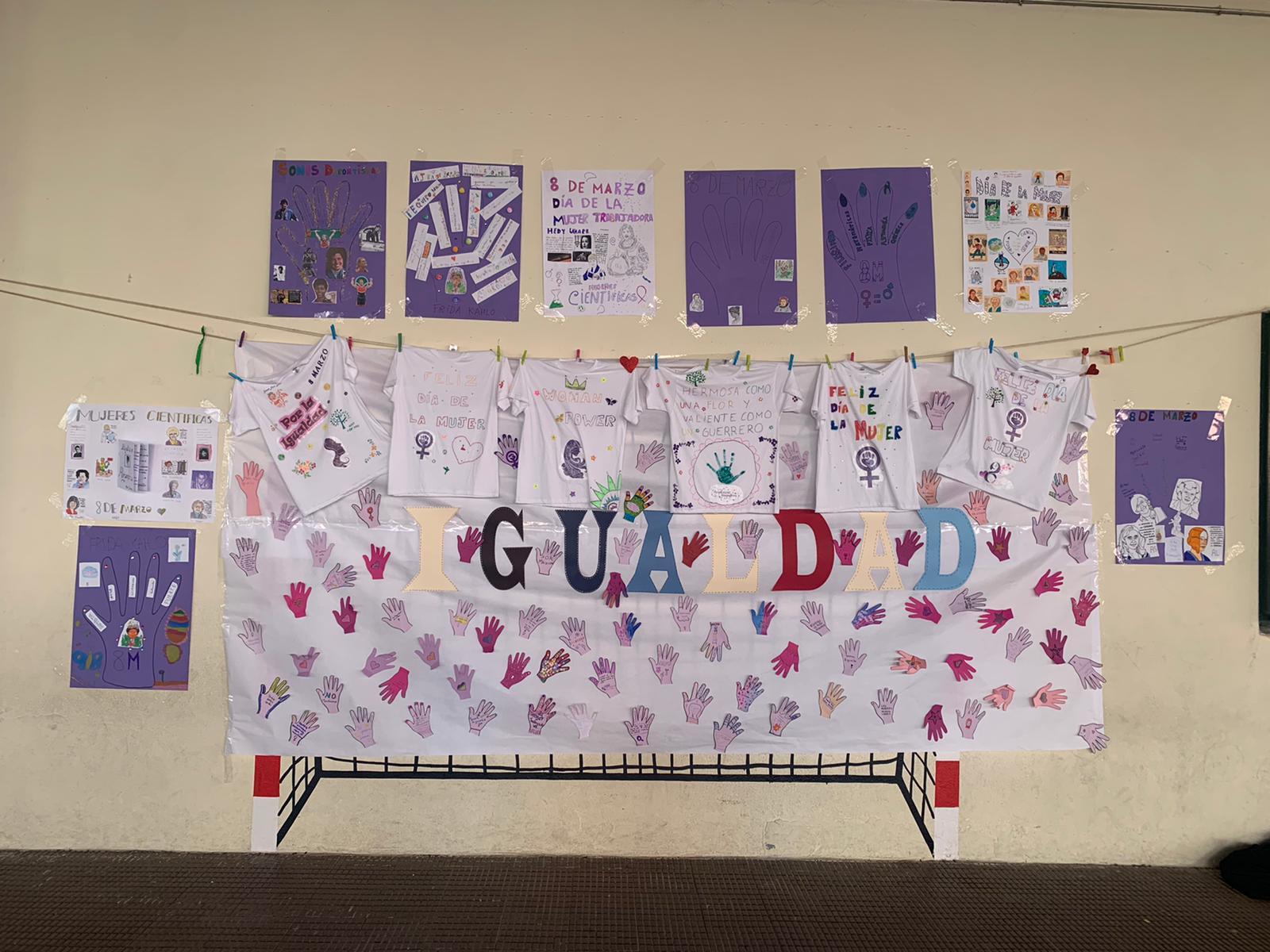 Carteles, camisetas y manos moradas con mensajes sobre el 8M sobre una pancarta que pone IGUALDAD.